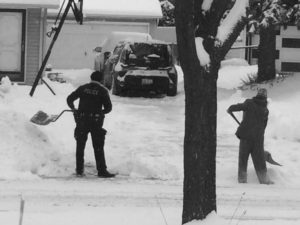 Police officer helps citizen shovel